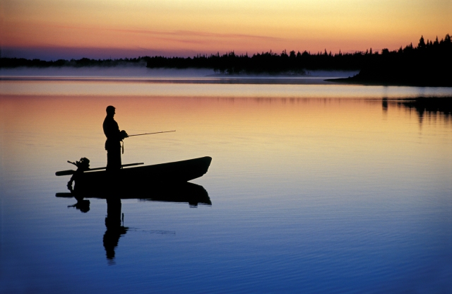 Silhouette of a man fishing from a small boat at dusk