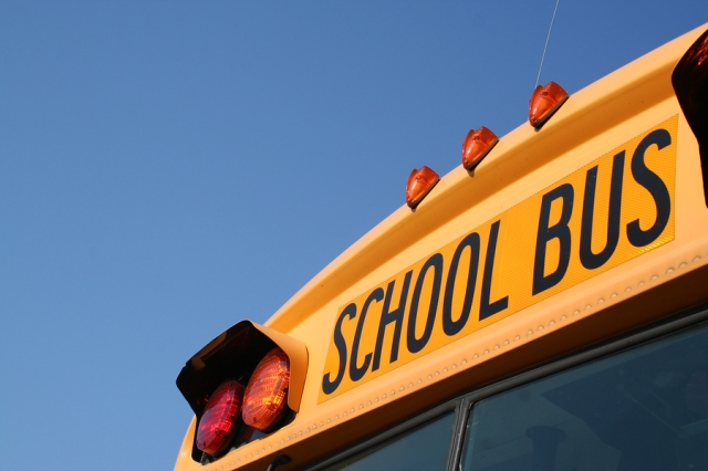 Close up of the front top of a school bus with the words school bus prominently displayed