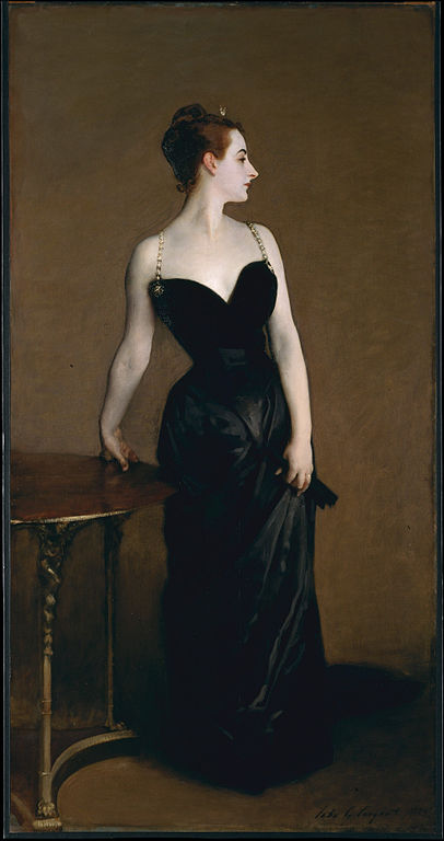 Portrait of beautiful woman in sleeveless black gown standing by table. One hand on table, face turned in profile
