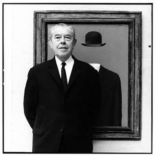 Photograph of Rene Magritte, in front of his painting The Pilgrim, as taken by Lothar Wolleh