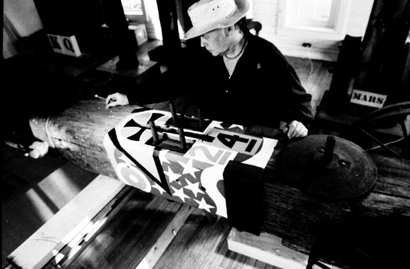 Black and white photo of American Artist Robert Indiana at work in a pensive mood. Taken in profile, Mr. Indiana is studying work, in progress
