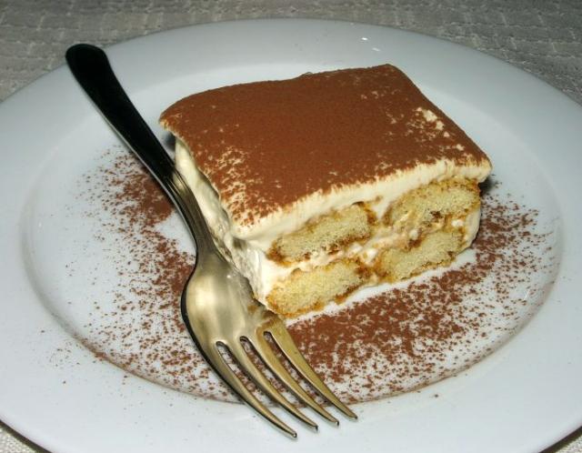 Tiramisu with fork on white dessert plate