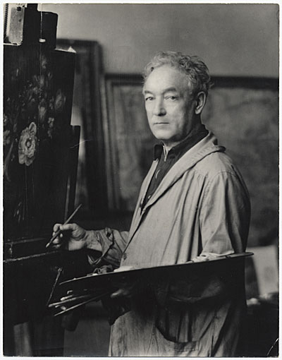 Photo of William Glackens in an artist's smock standing before an easel with paint brush and palette