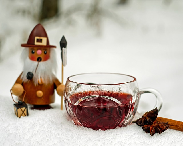 Mulled wine in a clear tea cup on a bed of artificial snow with cinnamon stick in the foreground, old world Christmas figure  in background holding lantern